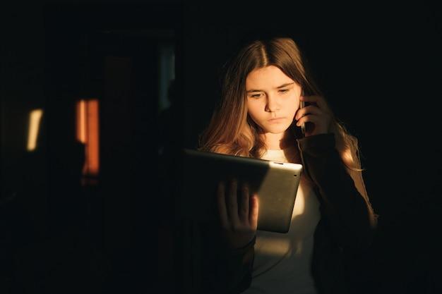 インターネットを悪用してコンピュータのラップトップの夜の前に座っているティーンエイジャーの女の子