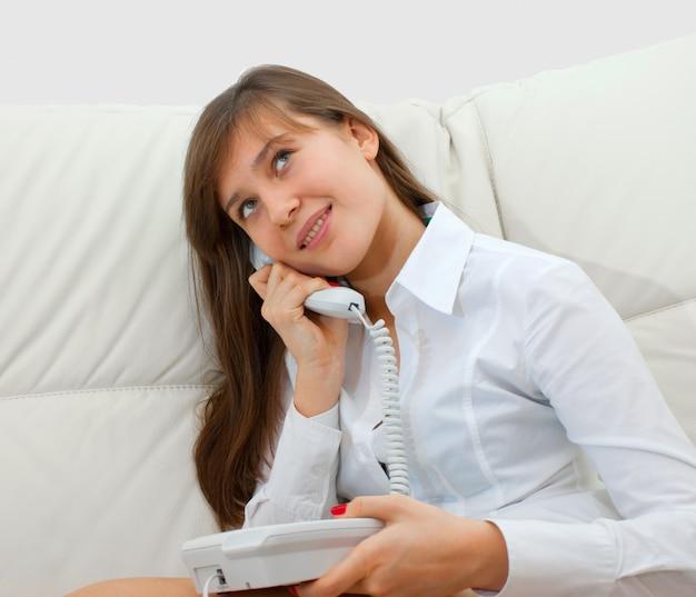 Девушка-подросток сидит на диване и разговаривает по телефону