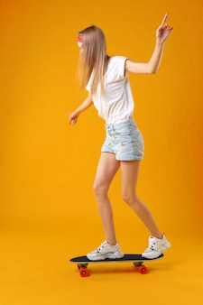 Teenager girl standing and posing on skateboard over a color background