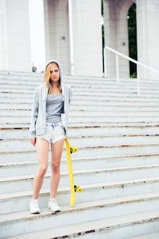 Девушка-подросток, стоя с скейтбордом