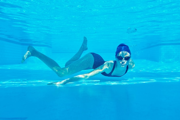 Teenager girl in swimsuit with goggles and swimming cap swimming underwater in pool