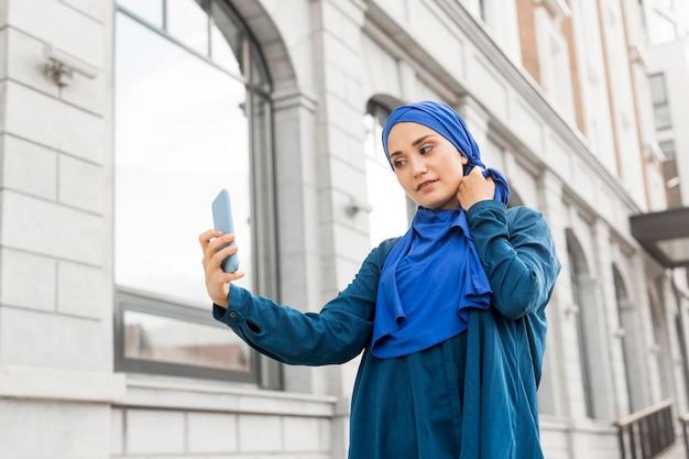 屋外で、selfieを取っているティーンエイジャーの女の子