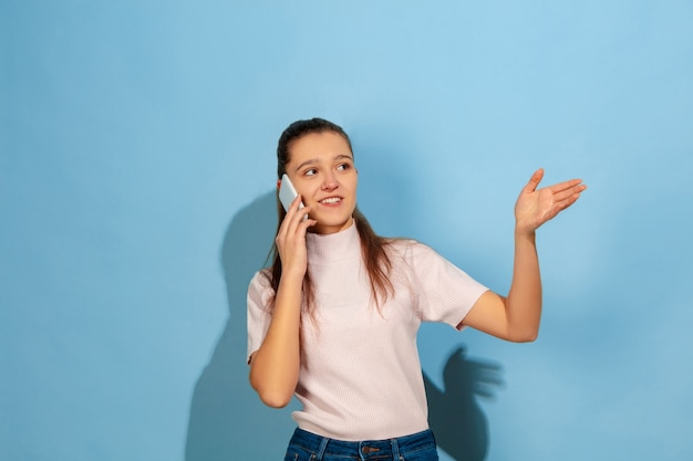 スマートフォンで話しているティーンエイジャーの女の子、笑顔