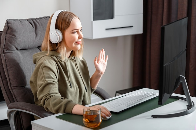 Teenager girl talking on video communication during remote online education using pc computer and headphones at home.casual woman waving her hand while talking via video call.