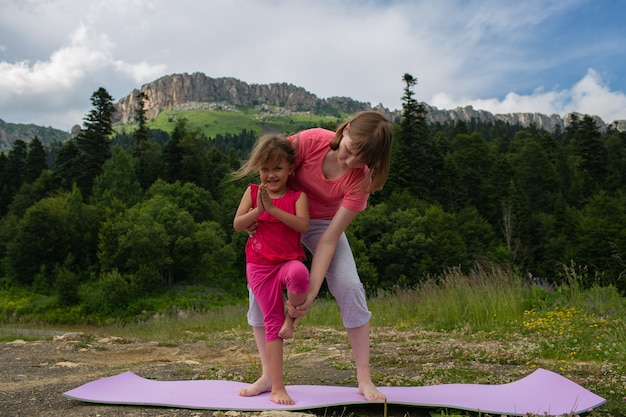 Teenager girl teaches a small child to do yoga exercises in nature on a background of mountains