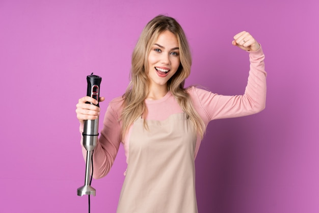 Teenager girl using hand blender isolated on purple wall doing strong gesture