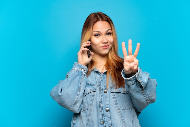 Teenager girl using mobile phone over isolated background happy and counting three with fingers