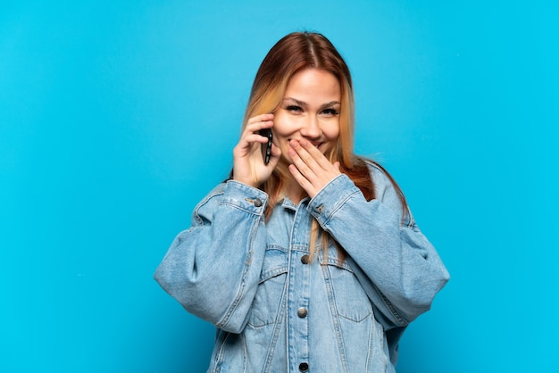 Teenager girl using mobile phone over isolated background happy and smiling covering mouth with hand