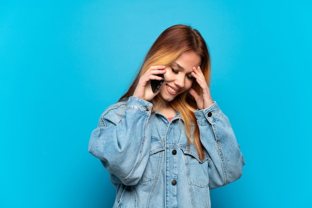 Teenager girl using mobile phone isolated background laughing