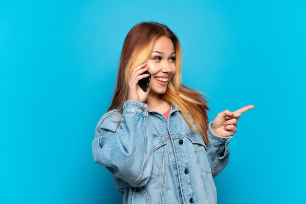 Teenager girl using mobile phone over isolated background pointing finger to the side and presenting a product
