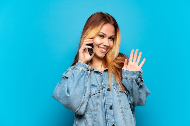 Teenager girl using mobile phone over isolated background saluting with hand with happy expression