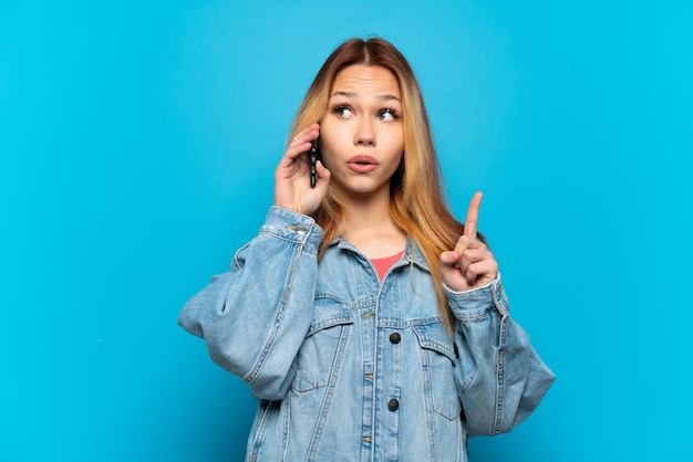 Teenager girl using mobile phone over isolated background thinking an idea pointing the finger up