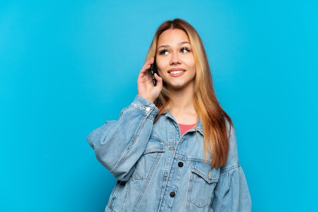 Teenager girl using mobile phone over isolated background thinking an idea while looking up