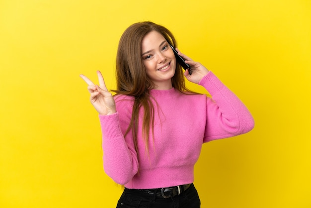 Teenager girl using mobile phone over isolated yellow background smiling and showing victory sign