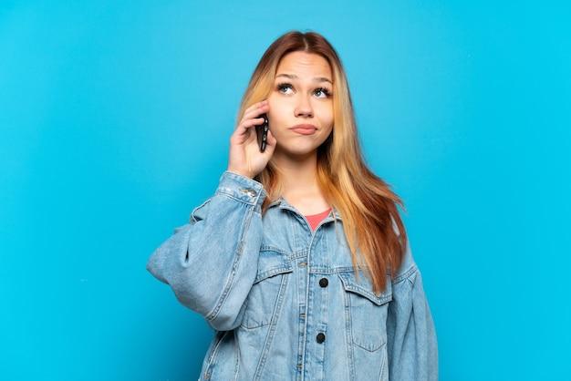 Девушка-подросток с помощью мобильного телефона на изолированном фоне и смотрит вверх
