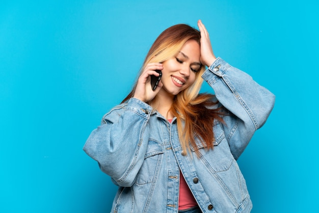 Девушка-подросток, использующая мобильный телефон на изолированном фоне, кое-что поняла и намеревается решить