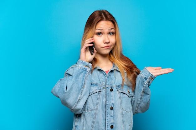 Девушка-подросток с помощью мобильного телефона на изолированном фоне, сомневаясь, поднимая руки