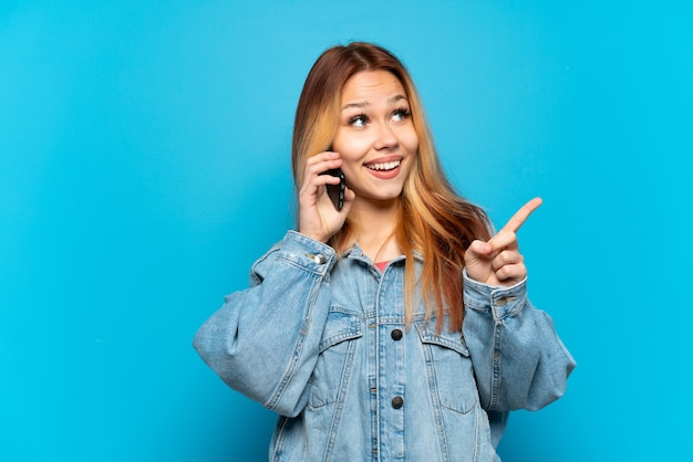 Девушка-подросток использует мобильный телефон на изолированном фоне, намереваясь реализовать решение, подняв палец вверх