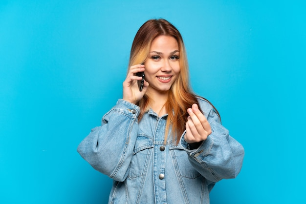 Девушка-подросток с помощью мобильного телефона на изолированном фоне, делая денежный жест