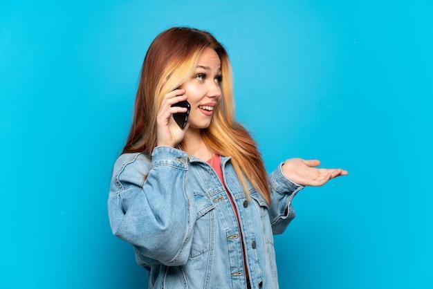 Девушка-подросток с помощью мобильного телефона на изолированном фоне с удивленным выражением лица, глядя в сторону