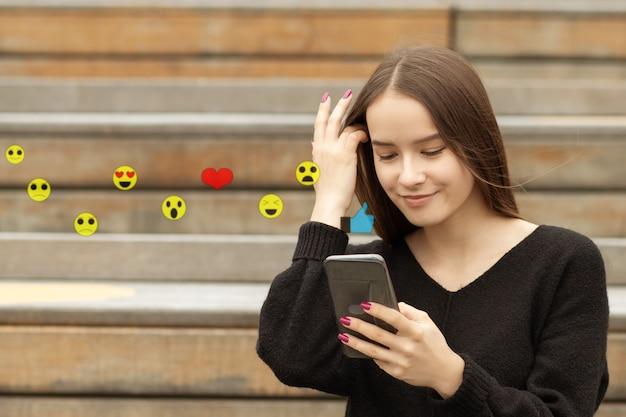 스마트폰을 사용하여 이모티콘을 보내고 비디오 라이브 스트리밍을 보는 10대 소녀