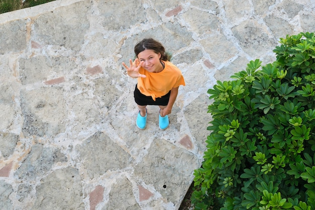 手を振って、歓迎し、カメラを見上げて、こんにちはジェスチャーを示すティーンエイジャーの女の子