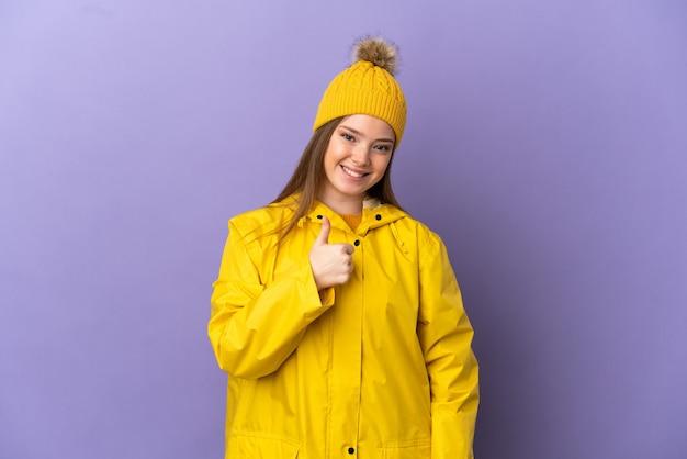 Девушка-подросток в непромокаемом пальто на изолированном фиолетовом фоне показывает палец вверх