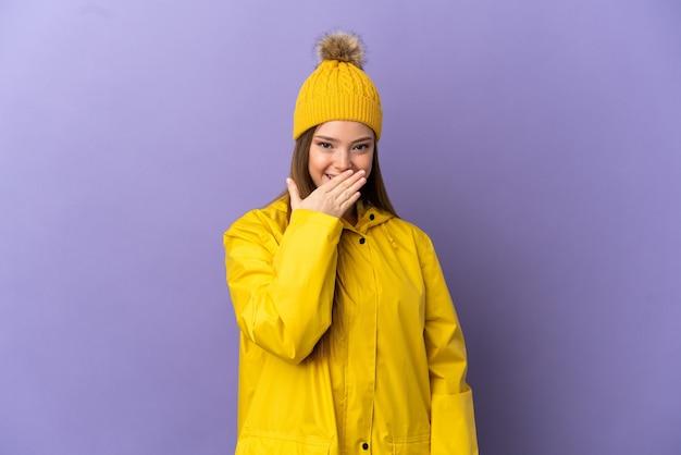 孤立した紫色の背景の上に防雨コートを着て幸せで笑顔の手で口を覆うティーンエイジャーの女の子