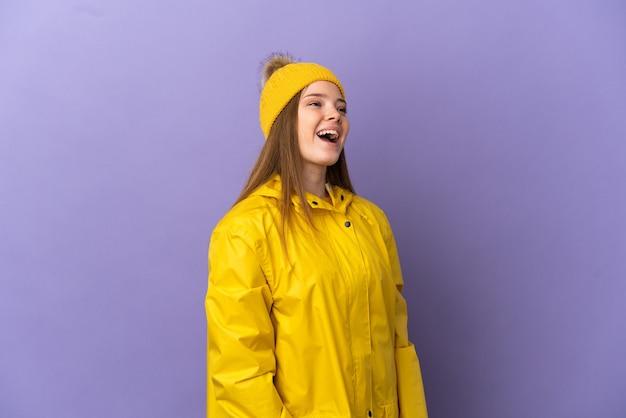 외진 보라색 배경 위에 방수 코트를 입고 옆으로 웃고 있는 십대 소녀