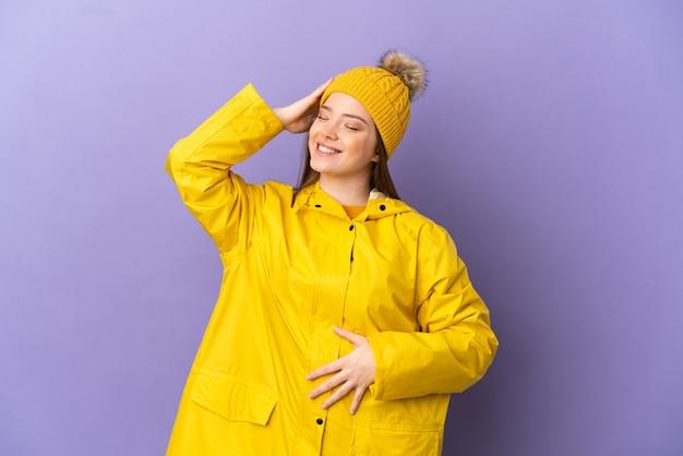 격리된 보라색 배경 위에 방수 코트를 입은 10대 소녀가 많이 웃고 있습니다.