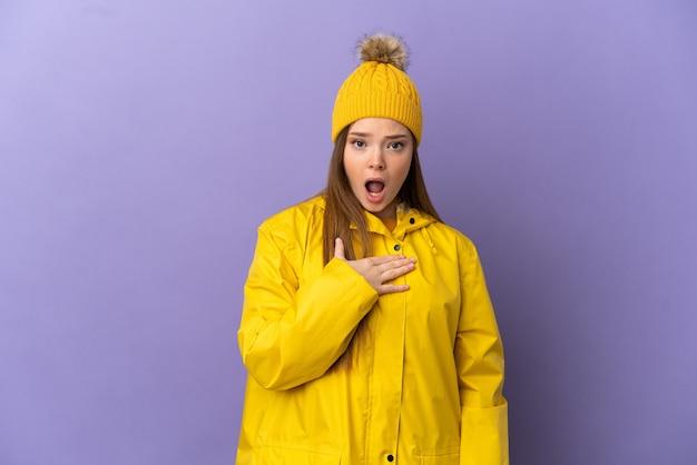 孤立した紫色の背景の上に防雨コートを着ているティーンエイジャーの女の子は、右を見ながら驚いてショックを受けました
