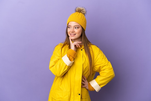 Девушка-подросток в непромокаемом пальто на изолированном фиолетовом фоне думает об идее, глядя вверх
