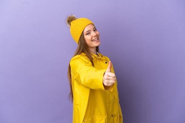 Девушка-подросток в непромокаемом пальто на изолированном фиолетовом фоне с большими пальцами руки вверх, потому что произошло что-то хорошее