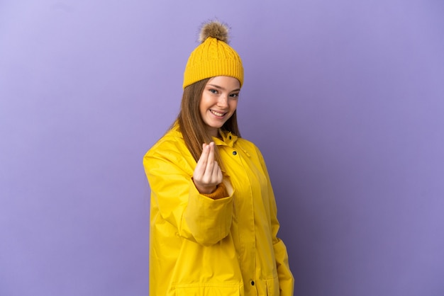Девушка-подросток в непромокаемом пальто над изолированной фиолетовой стеной делает денежный жест