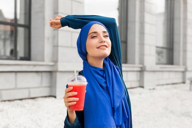 外で青いポーズを身に着けているティーンエイジャーの女の子