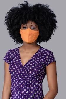 灰色の背景に分離されたcovid-19に対して顔の保護マスクを身に着けているティーンエイジャーの女の子