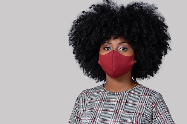 灰色の背景に分離されたcovid19に対して顔の保護マスクを身に着けているティーンエイジャーの女の子