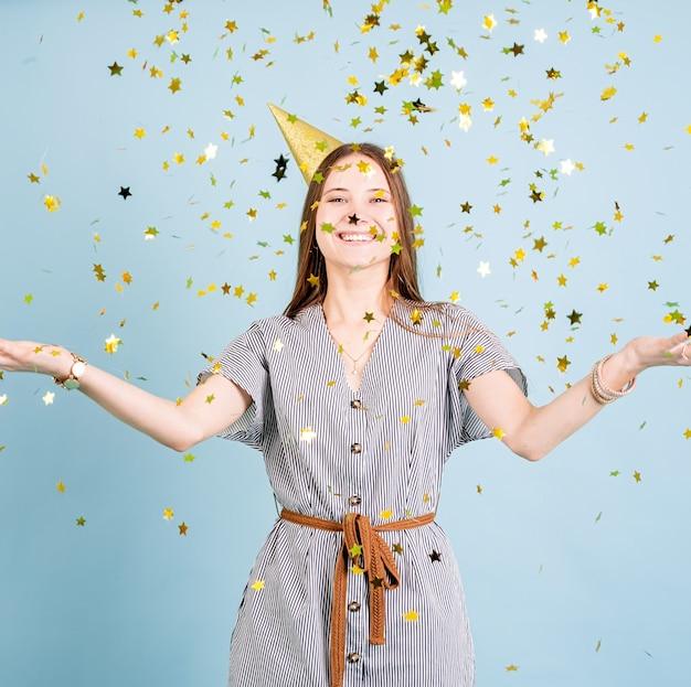 Девушка-подросток в золотой шляпе на день рождения, бросая конфетти