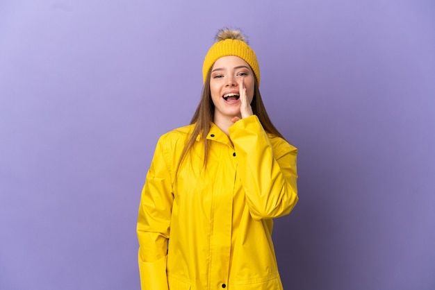 Teenager girl wearing a rainproof coat over isolated purple background shouting with mouth wide open