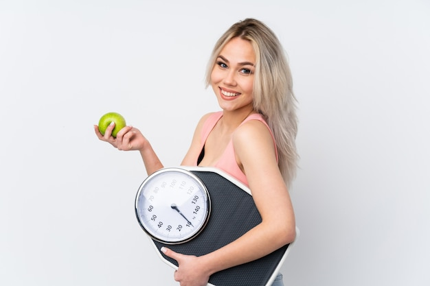 Teenager girl over white wall with weighing machine and with an apple