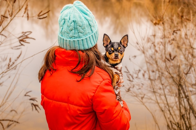 A teenager girl in a winter jacket and a hat with her back to the camera with a dog in her arms.