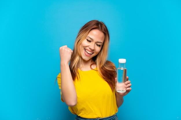 勝利を祝う孤立した青い背景の上に水のボトルを持つティーンエイジャーの女の子