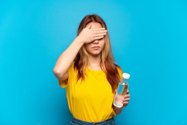 手で目を覆っている孤立した青い背景の上に水のボトルを持つティーンエイジャーの女の子。何かを見たくない