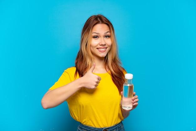 Девушка-подросток с бутылкой воды на синем фоне показывает палец вверх