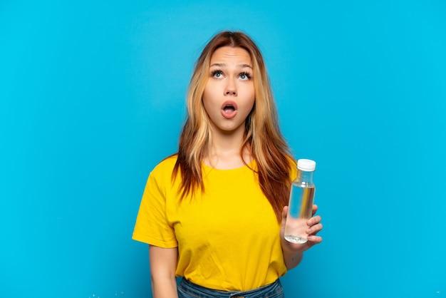 Девушка-подросток с бутылкой воды на изолированном синем фоне смотрит вверх и с удивленным выражением лица