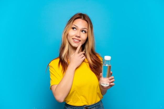 Девушка-подросток с бутылкой воды на изолированном синем фоне смотрит вверх, улыбаясь
