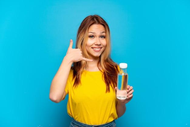 Девушка-подросток с бутылкой воды на изолированном синем фоне, делая жест телефона. перезвони мне знак