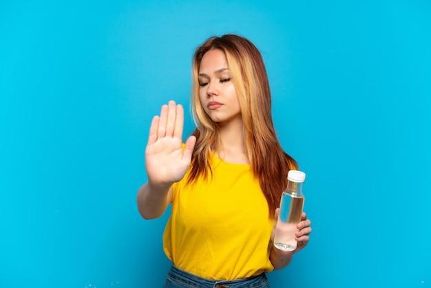 격리 된 파란색 배경 위에 물 한 병을 가진 십 대 소녀 중지 제스처를 만들고 실망