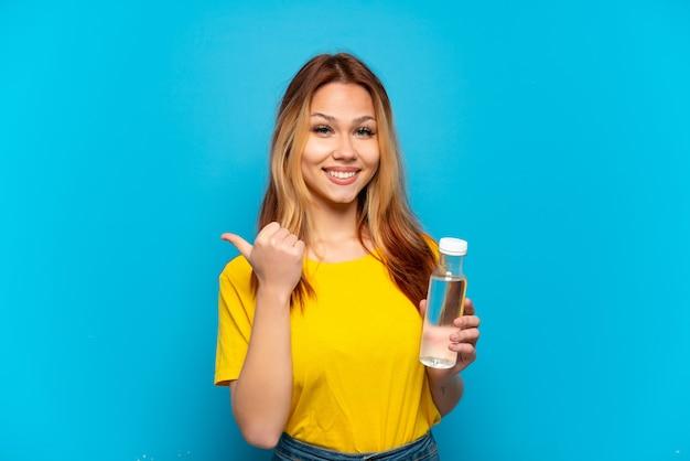 Девушка-подросток с бутылкой воды на изолированном синем фоне, указывая в сторону, чтобы представить продукт