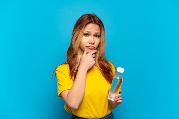 Девушка-подросток с бутылкой воды на изолированном синем фоне мышления